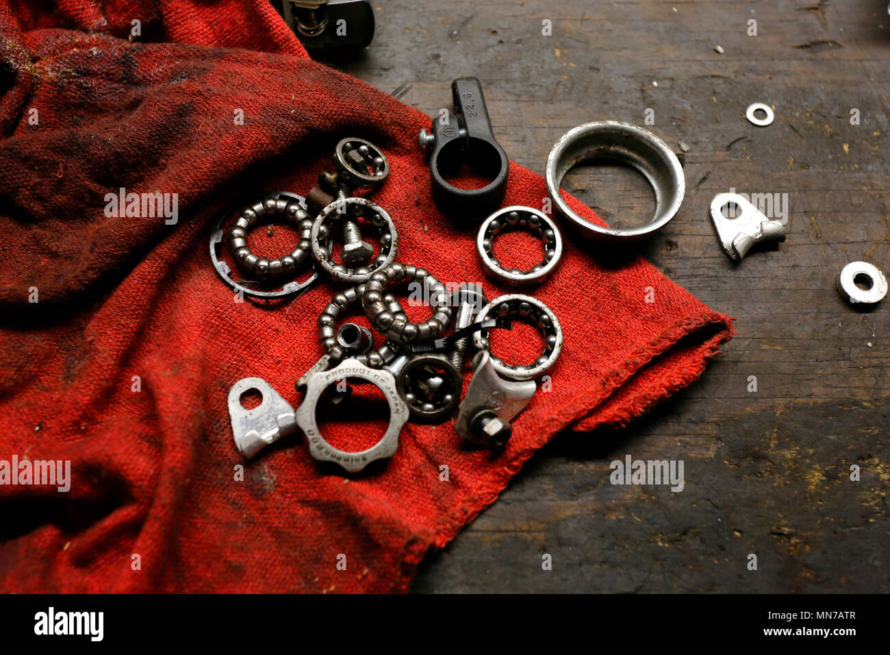 Ball bearings, washers, and other mechanical parts on top of a grease stained table - Stock Image