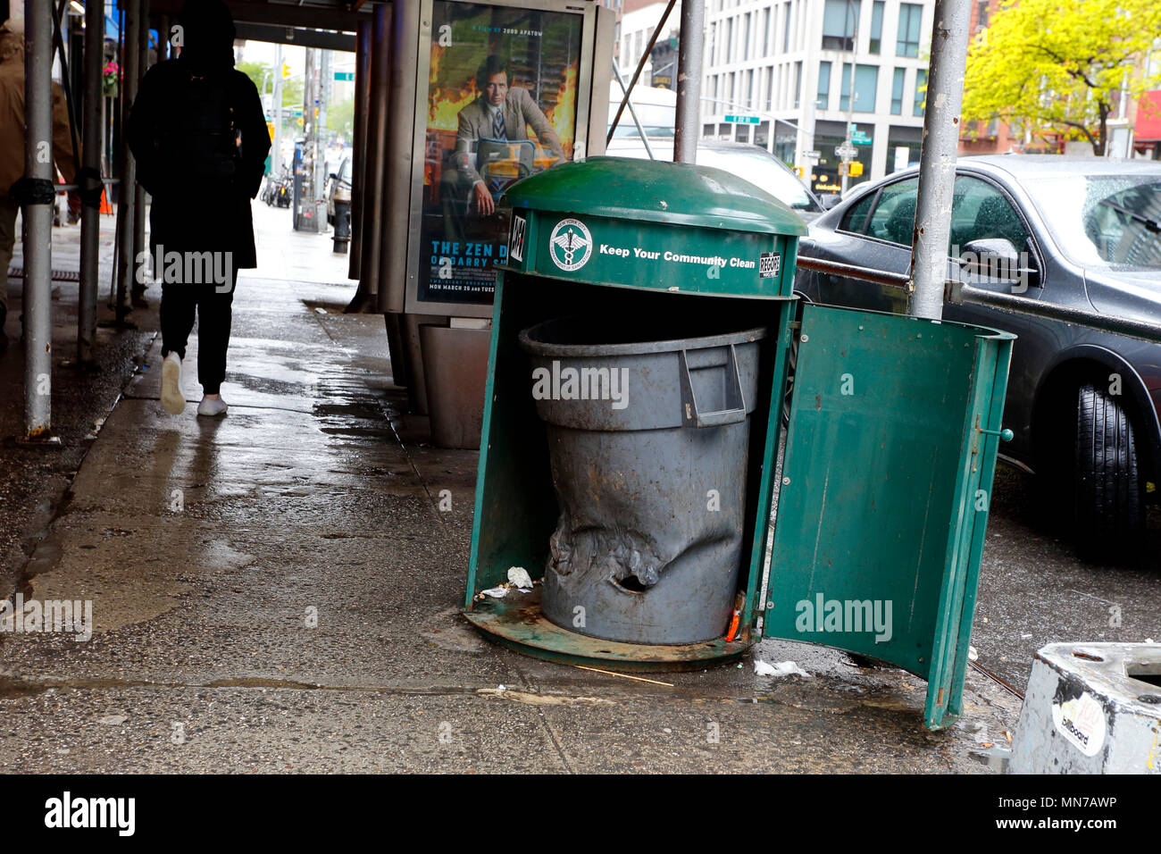 A partially melted plastic garbage collection bin inside a NYC garbage can - Stock Image