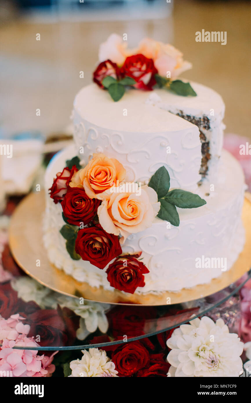Vertical View Of The White Wedding Cake Decorated With Red And