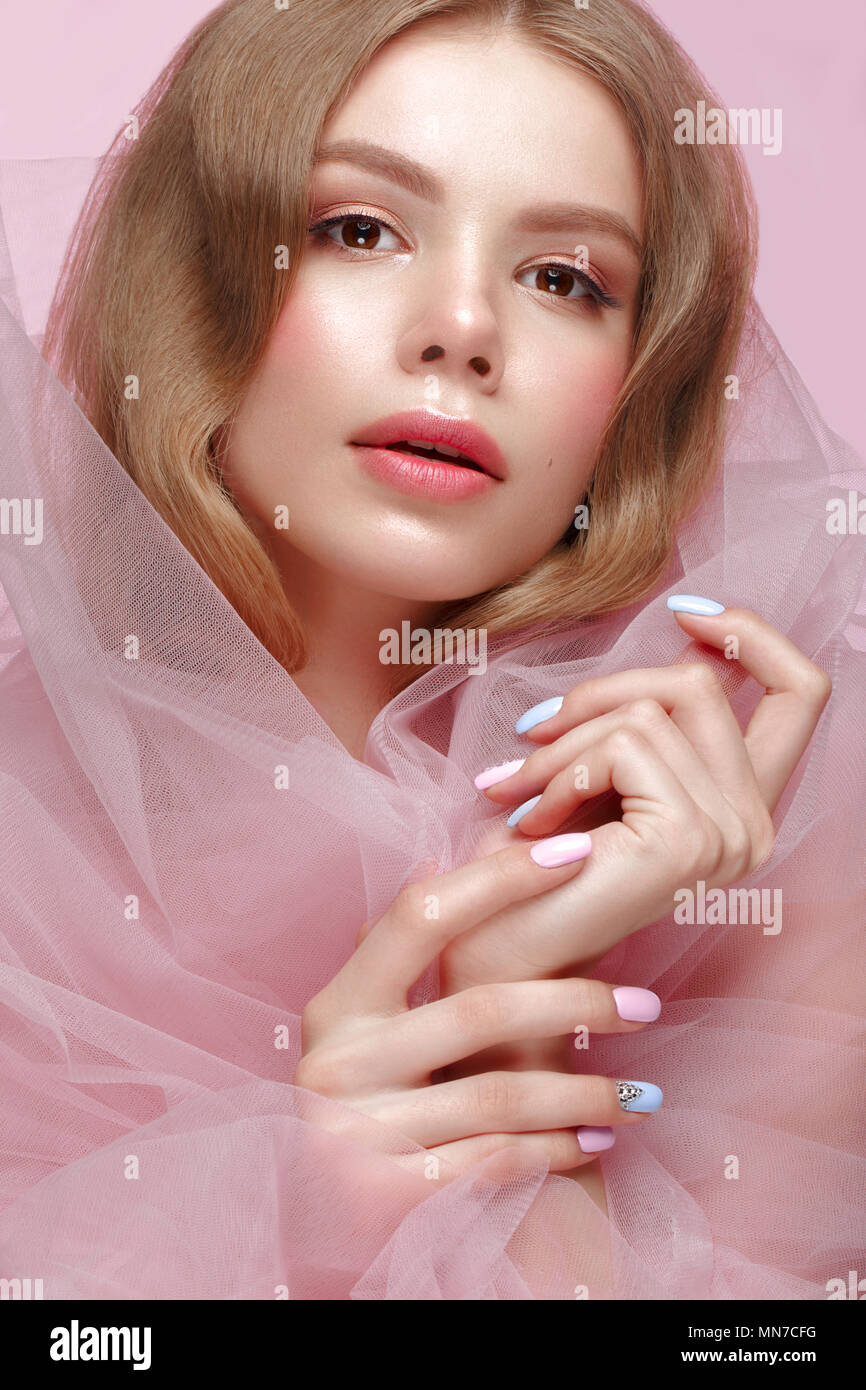 Beautiful girl with light make-up and gentle manicure in pink clothes. Beauty face. Design nails. - Stock Image
