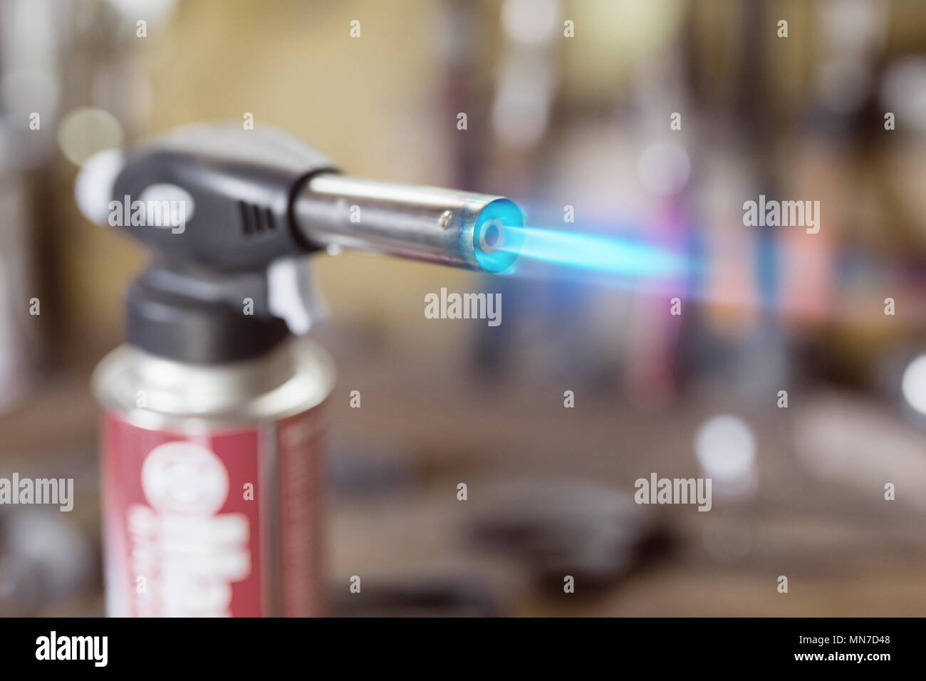 Gas cartridge gun lighter .Close-up nozzle of burner with blue f - Stock Image
