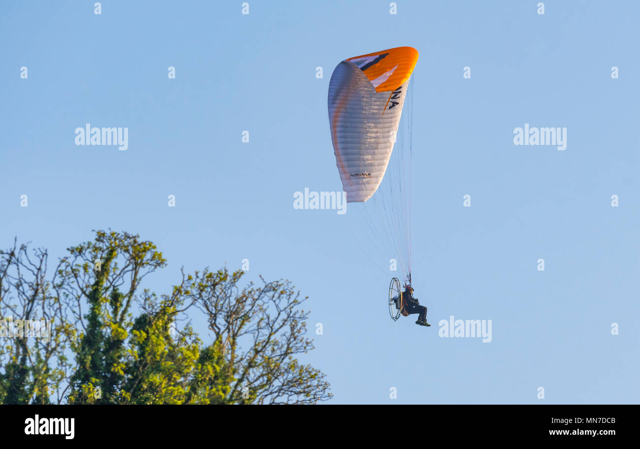 Powered paragliding, also known as paramotoring, a single engine one person powered glider above trees in the UK. - Stock Image