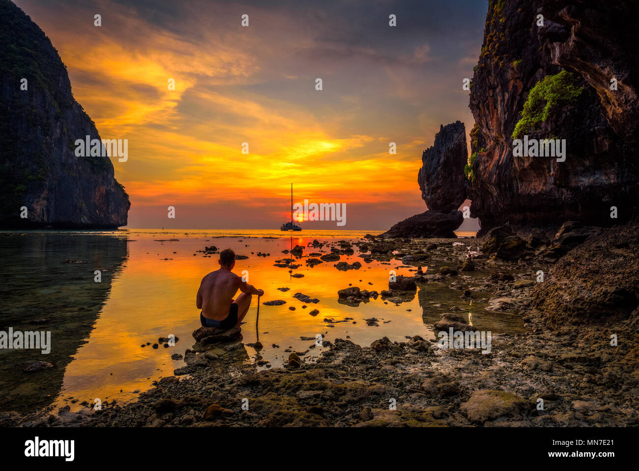 Young boy enjoys dramatic sunset at Maya beach in Thailand - Stock Image
