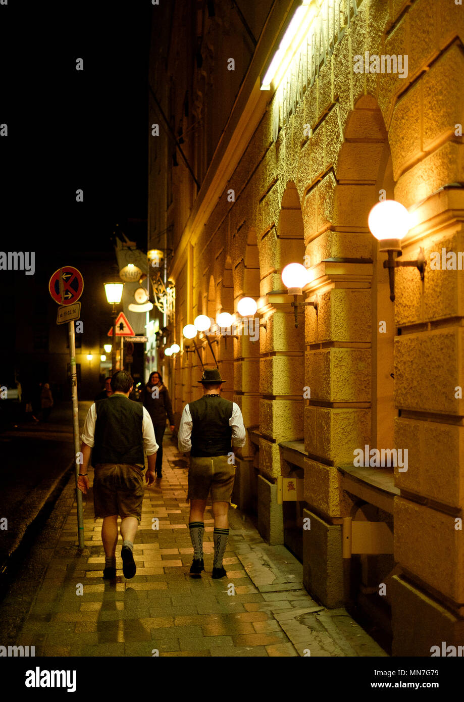 Two men in lederhosen on the streets of the old town Munich at night - Stock Image