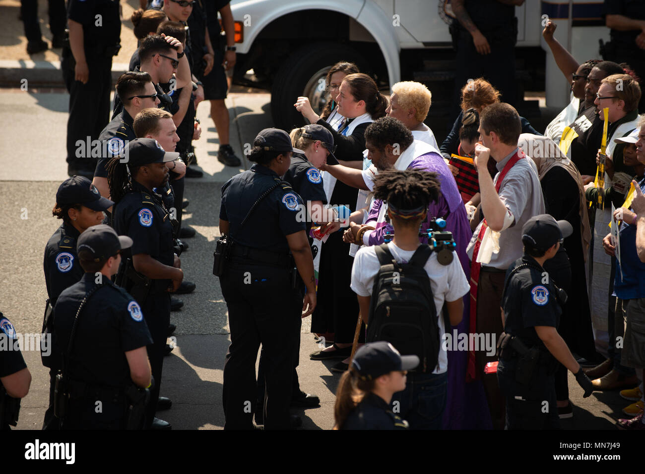 Washington, DC, USA. 14th May, 2018. THE REV. WILLIAM BARBER (in purple) and THE REV. LIZ THEOHARIS are among the first to be arrested at a rally and march launching a new Poor People's Campaign at the U.S. Capitol in Washington, DC. The campaign, modeled after a similarly named campaign by the Rev. Dr. Martin Luther King 50 years earlier, began with rallies in about three dozen states, and is planned to last six weeks. Approximately 200 people were arrested in the various rallies, often being cited for blocking traffic. Credit: Jay Mallin/ZUMA Wire/Alamy Live News Stock Photo