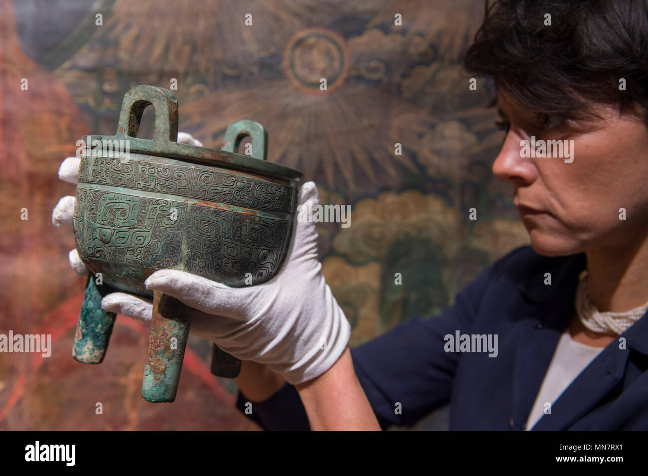Bonhams, New Bond Street, London, UK. 15 May, 2018.  Bonhams Chinese Art expert holds a very rare archaic bronze ritual food vessel, Ding, Late Shang Dynasty (12th/11th c.) at Bonhams Fine Chinese and Fine Japanese Art Sale preview, estimated £180,000-240,000. Credit: Malcolm Park/Alamy Live News. - Stock Image