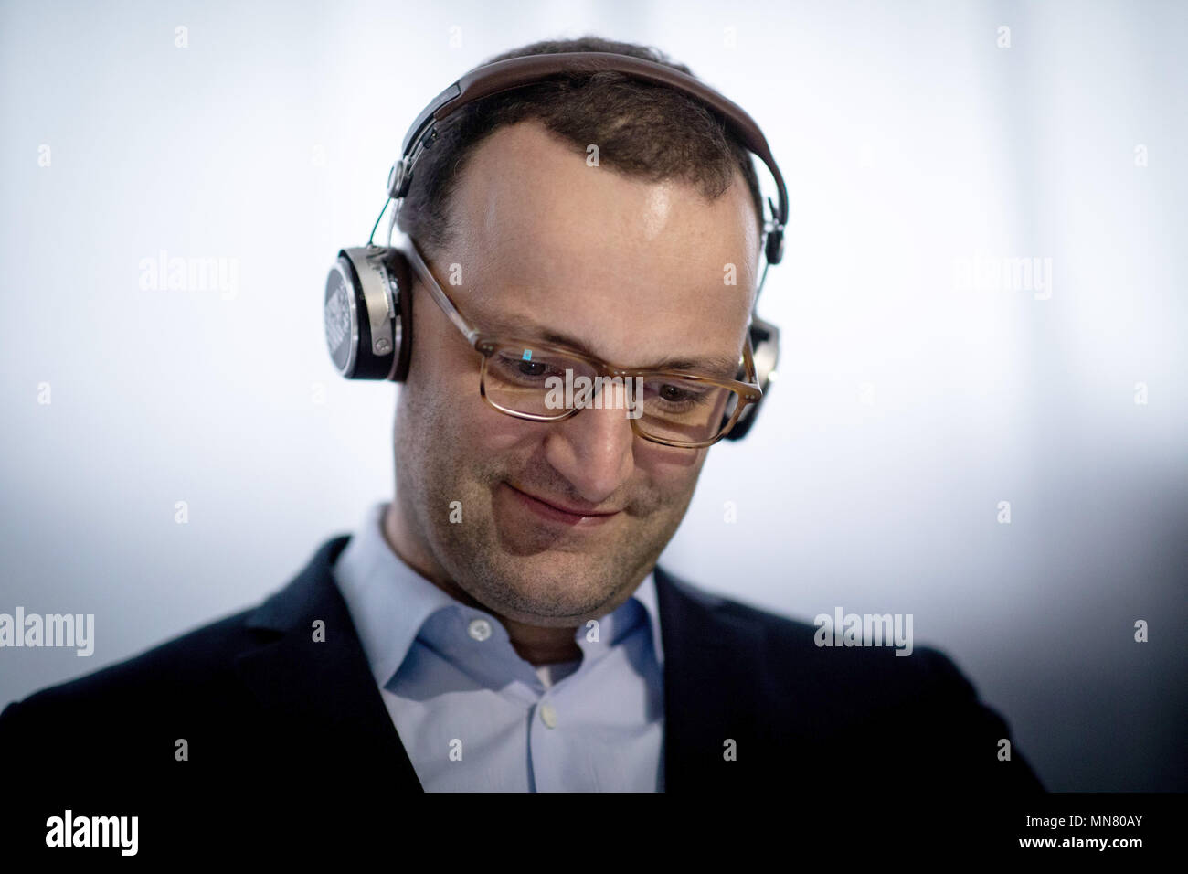 15 May 2018, Berlin, Germany: Jens Spahn of the Christian Democratic Union (CDU), Federal Health Minister, during a visit to the StartUp trade fair 'Cube Tech Fair', tests a headset for the early detection of a hearing impairment at the Mimi booth. Spahn participated in a discussion on 'Digitizing the Healthcare Industry through Blockchain and Artificial Intelligence.' Photo: Kay Nietfeld/dpa - Stock Image