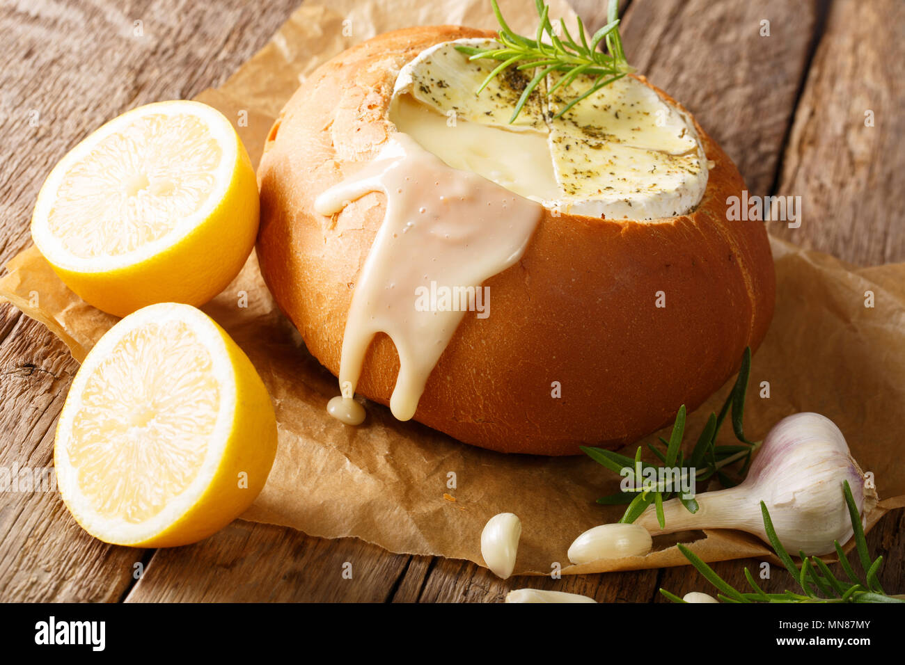 Rustic fondue in bread with melted camembert cheese close-up on the table. horizontal - Stock Image