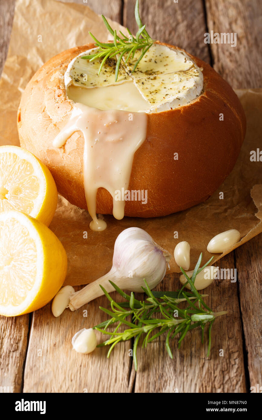 Fondue in a loaf of bread from melted camembert cheese close-up on a table. vertical - Stock Image