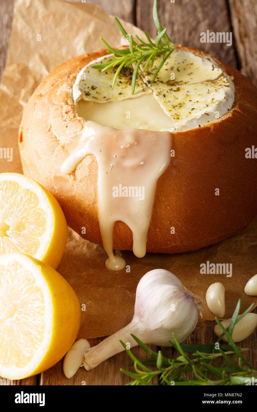 loaf of bread stuffed with melted Camembert cheese close-up on a table. vertical - Stock Image