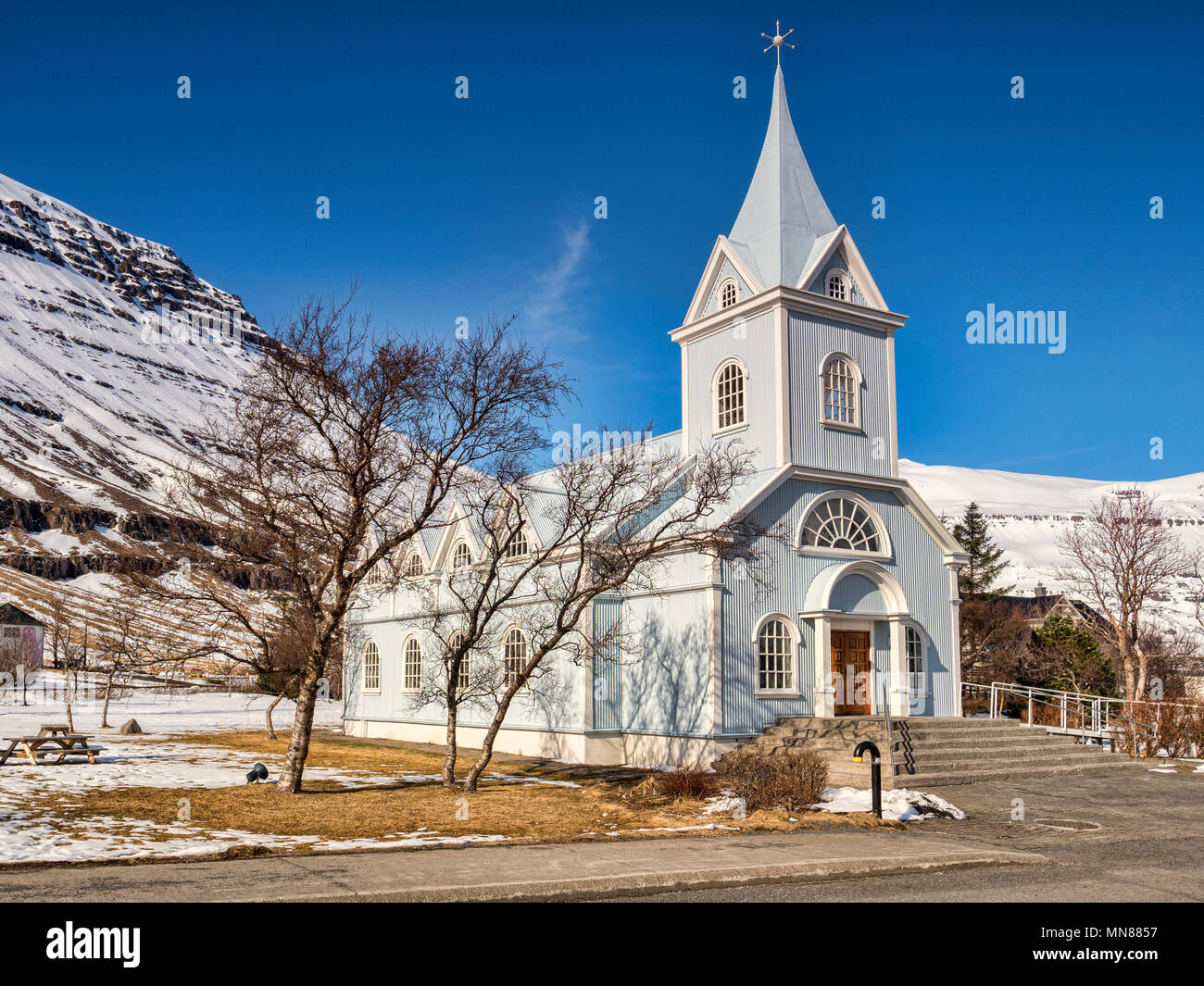 The famous Blue Church at Seydisfjordur, East Iceland, on a bright spring day with snowy mountains. - Stock Image