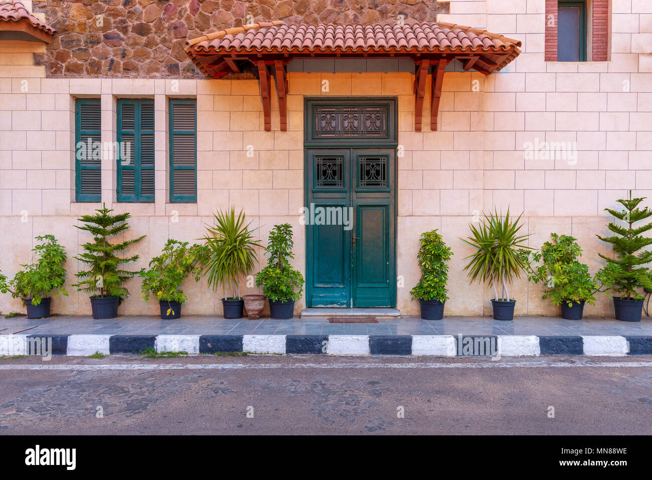 Facade of the clock tower in Montaza public park with green wooden door with red tile canopy above and window shutters on stone bricks wall, Alexandri - Stock Image
