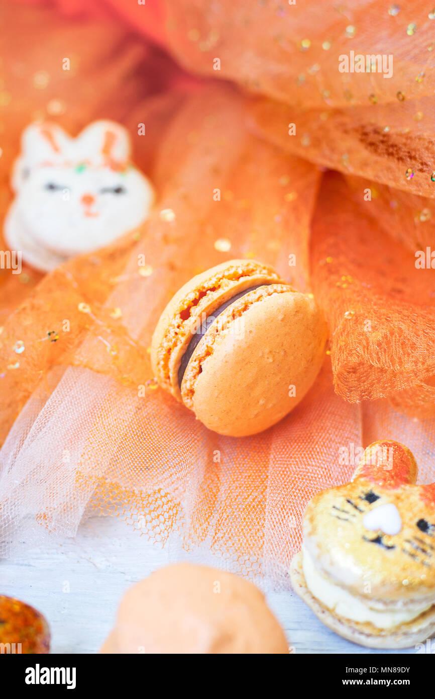 Orange macaroons with chocolate filling on orange tulle background Stock Photo