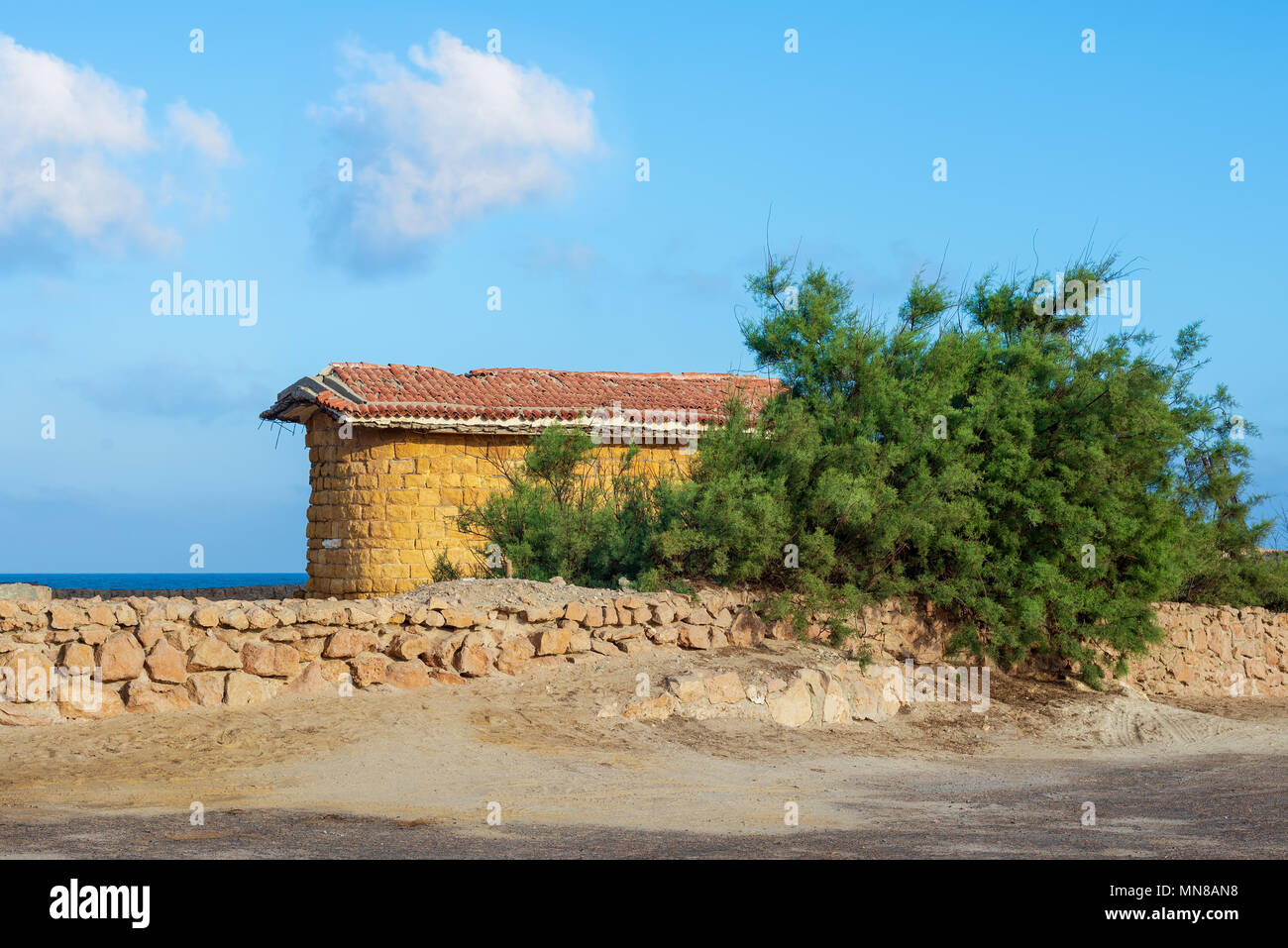 Abandoned building built of stone bricks and red tiled roof, short green tree and stone fence on background of partly cloudy sky and calm sea, Montaza - Stock Image