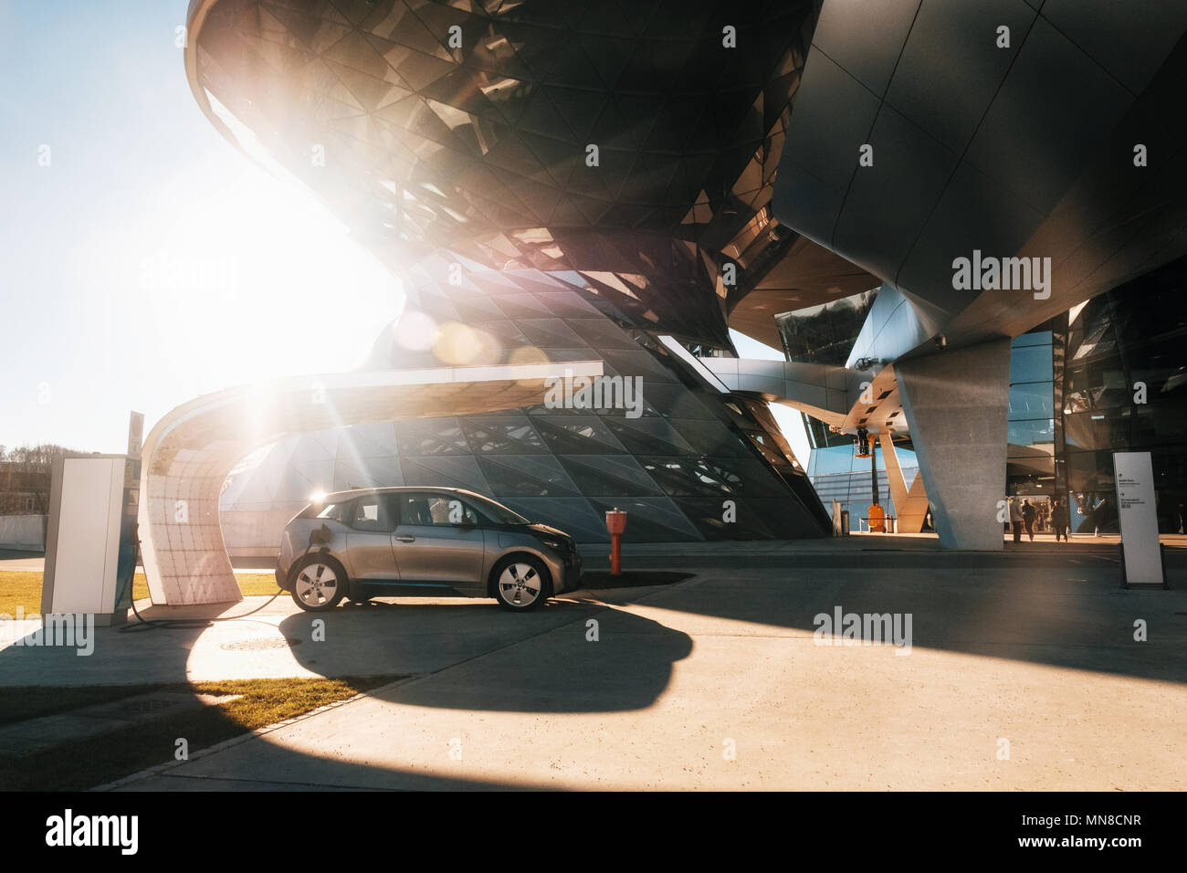 Munich, Germany - December 7, 2017: BMW i3 electric car standing at a charging station at BMW Welt World of BWM with exhibition and museum buildings a - Stock Image
