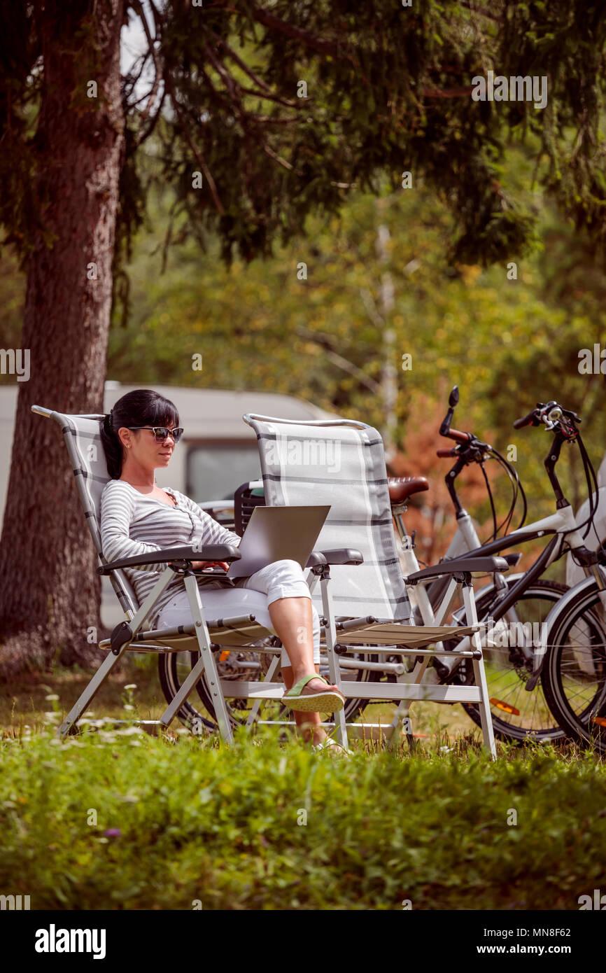 Woman looking at the laptop near the camping   Caravan car