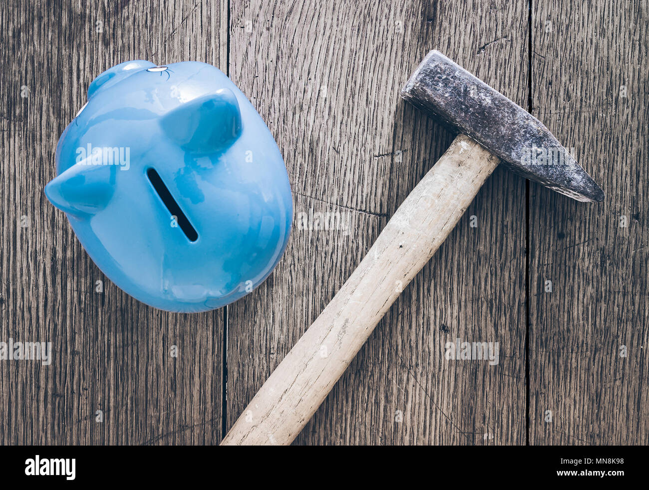 top view of hammer and piggy bank on wooden table, lack of money concept Stock Photo