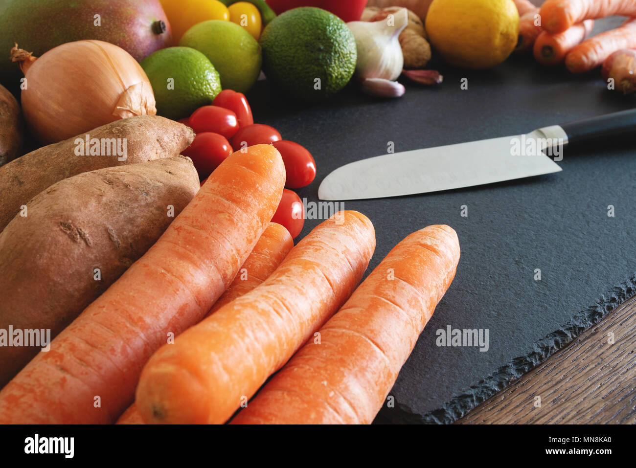 fresh organic fruits and vegetables on slate cutting board with kitchen knife - Stock Image
