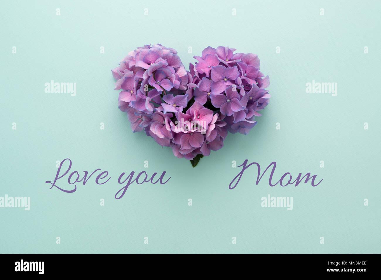 Text Love You Mom Heart Shape Made Of Purple Flowers On Blue