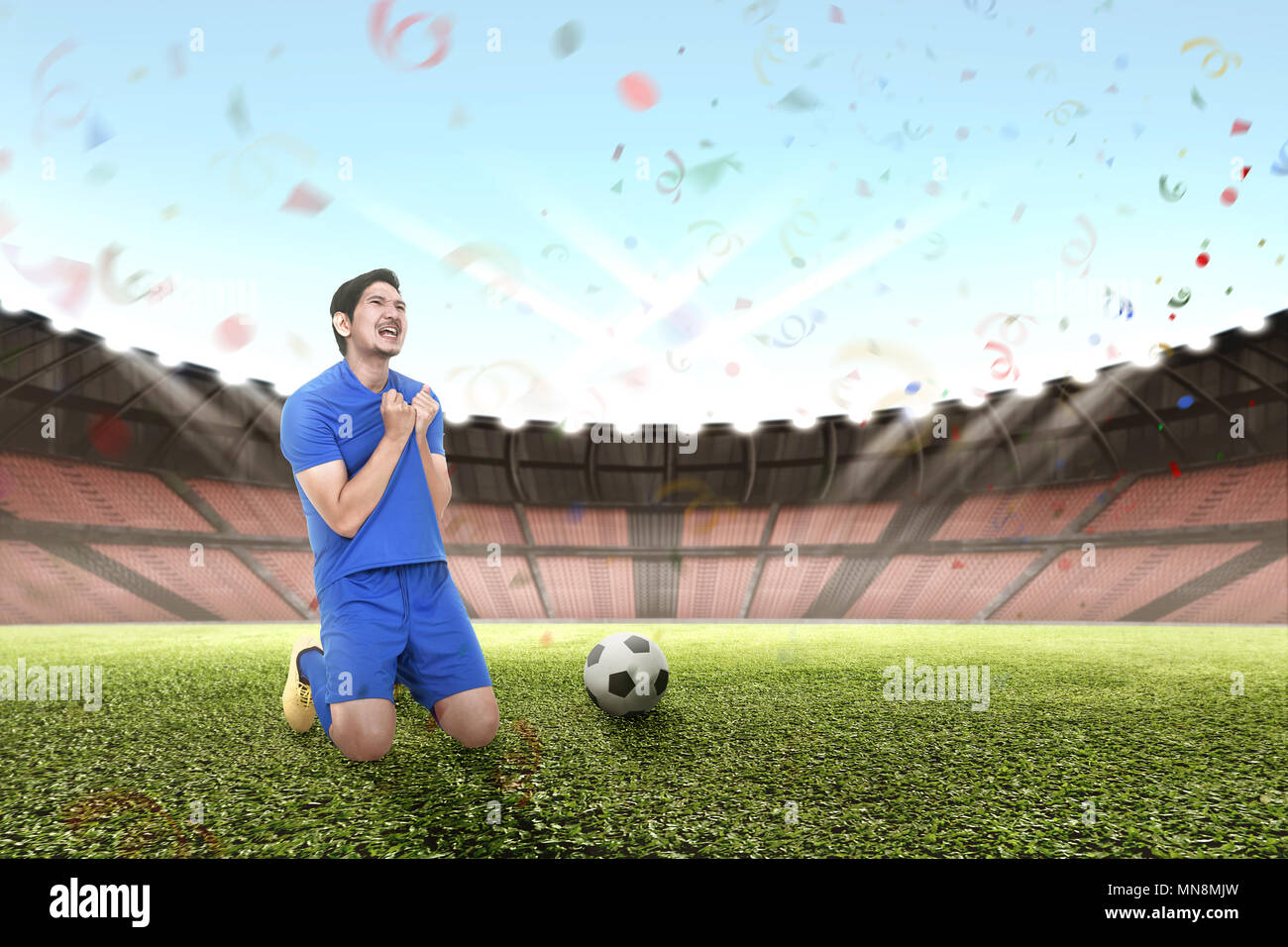 Cheerful asian footballer celebrating victory on the stadium - Stock Image