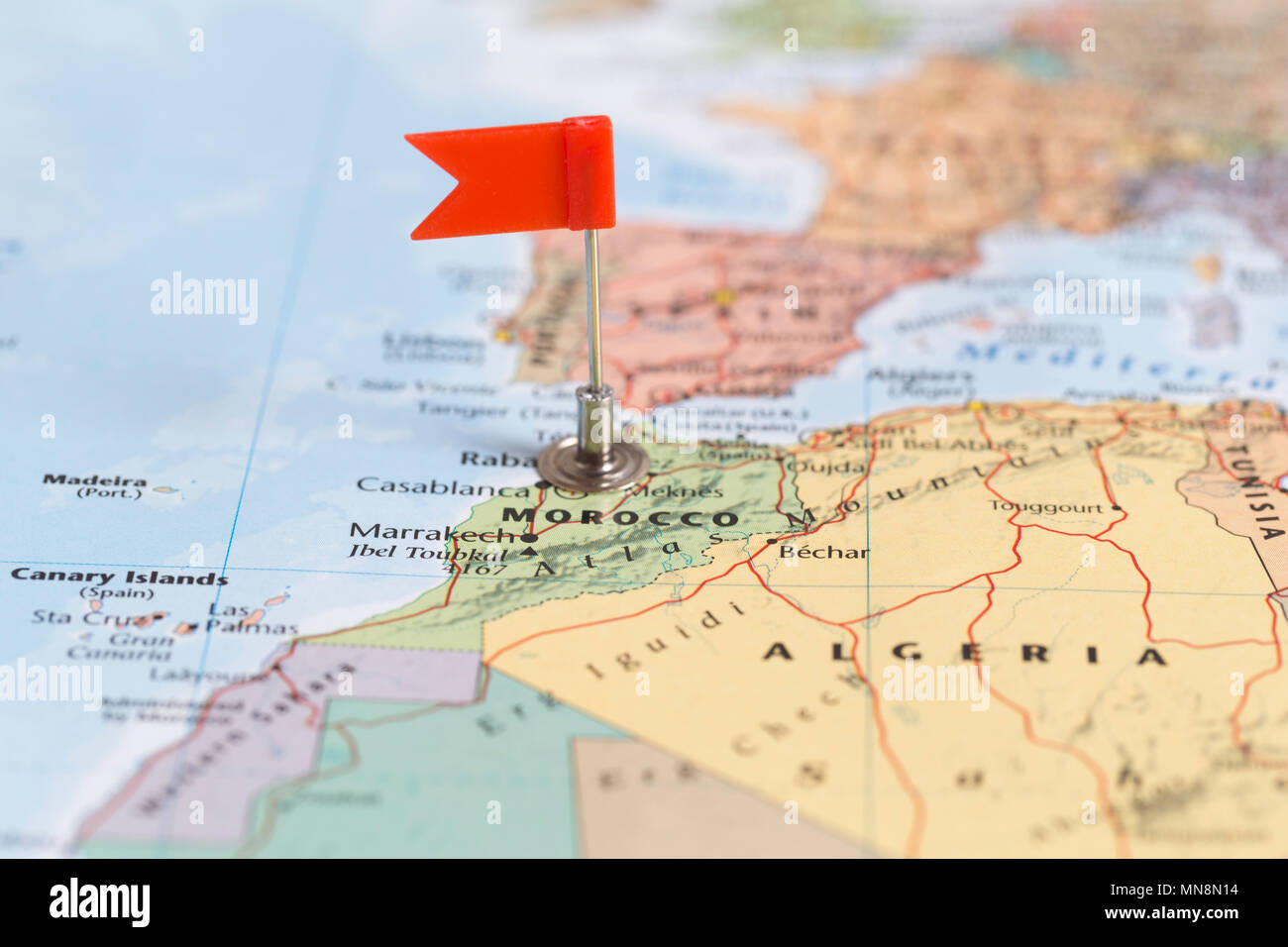 Small red flag marking the African country of Morocco on a world map ...