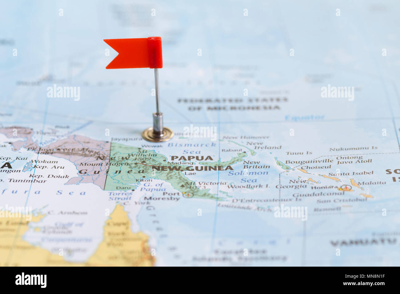 Small Red Flag Marking Papua New Guinea On A World Map Stock Photo