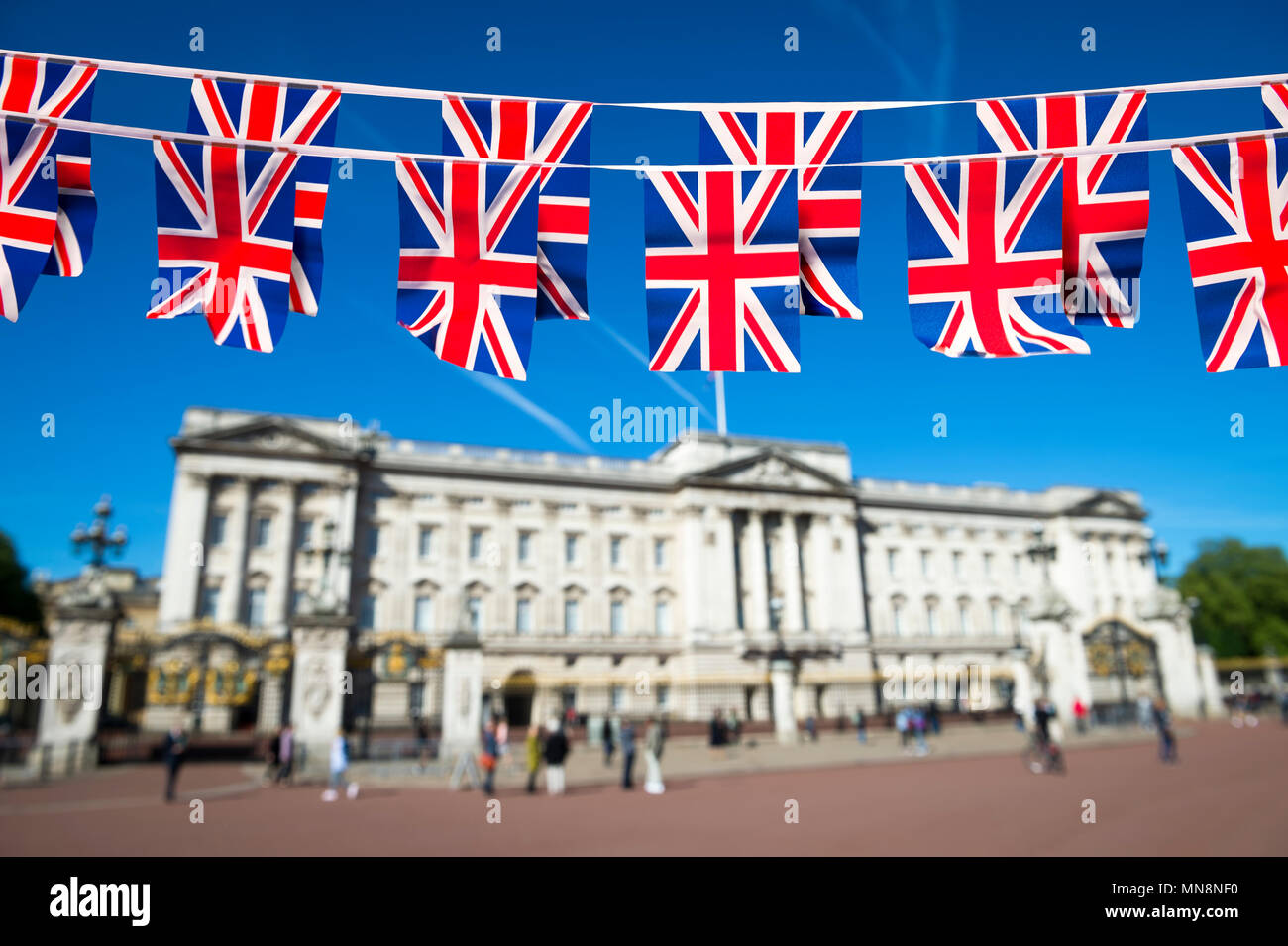Union Jack flag bunting decorates the Mall in front of Buckingham Palace ahead of the Royal Wedding in London, England. - Stock Image