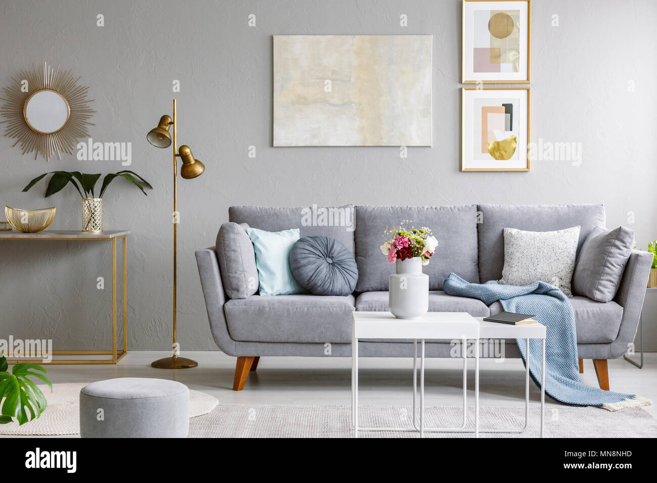 Gold Mirror Above Shelf With Plant In Grey Living Room Interior Sofa And Flowers On Table Real Photo