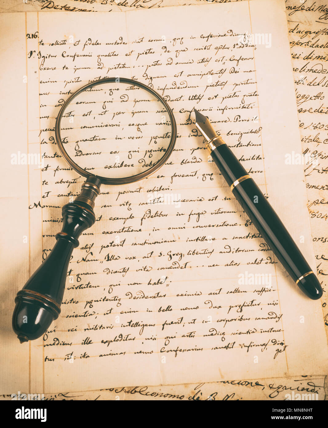 Fountain pen and magnifying glass on a letter - Stock Image