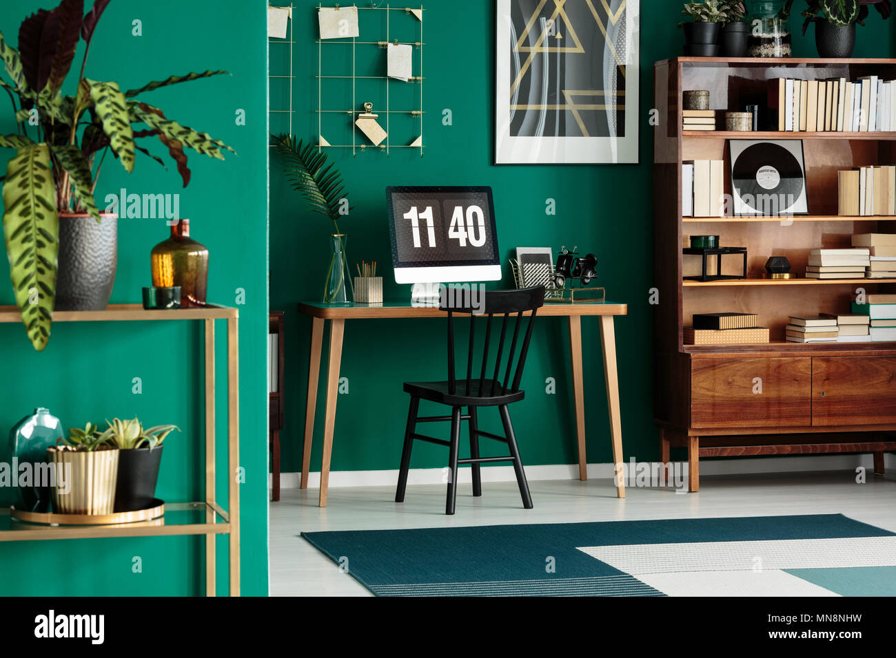 Black chair at desk with desktop computer in green home office interior with wooden furniture - Stock Image
