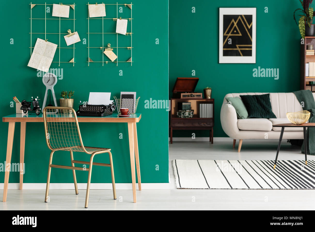 Gold chair at desk with typewriter in freelancer's open space interior with settee against emerald green wall - Stock Image
