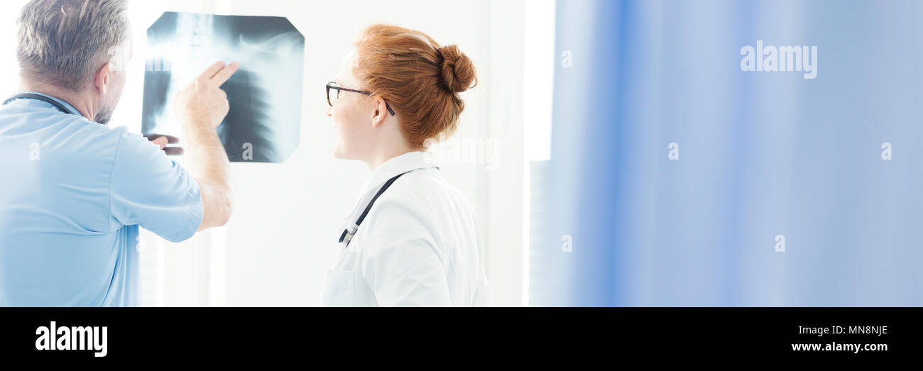 Header with an orthopedist consulting a broken bone with his female colleague, pointing to a shoulder on an X-ray test results - Stock Image