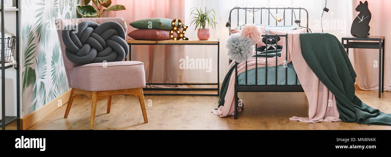 Two grey and pink pompoms hanging on a metal bed frame in cozy bedroom interior with knot cushion on armchair Stock Photo