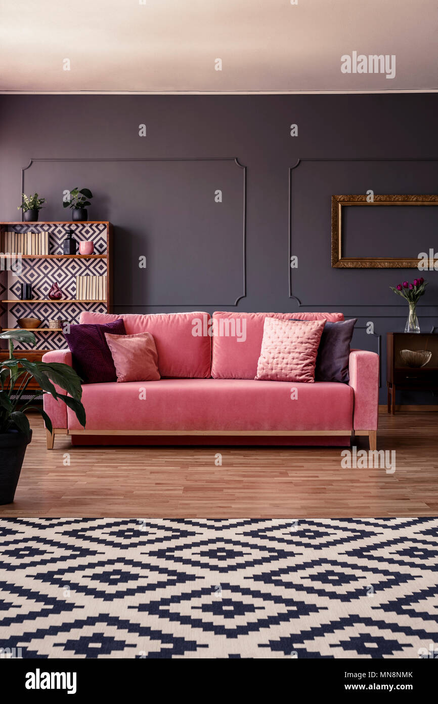 Pink Velvet Couch With Cushions Standing In The Middle Of Dark Grey