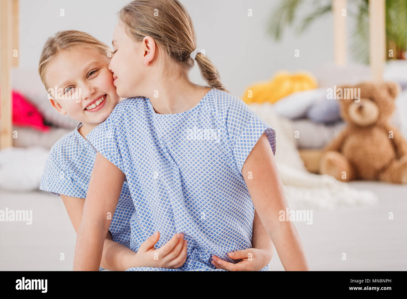 Two loving sisters wearing blue dresses hugging each other Stock Photo