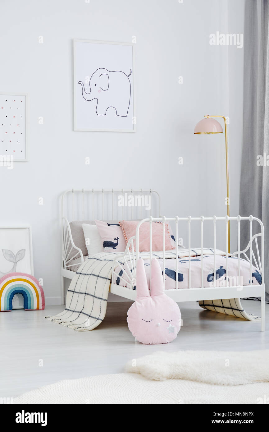 Pink pillow next to white bed in girl\'s bedroom interior ...