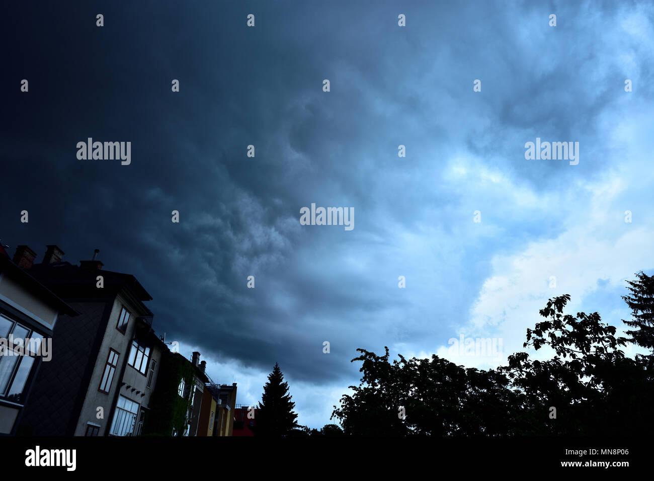 Huge dark cumulonimbus thundercloud time-lapse over the outskirts of Vienna, Austria. Thunderstorm darkens the evening sky. - Stock Image