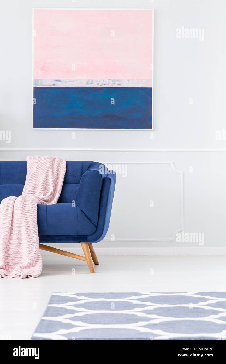 Pink blanket on navy blue sofa against white wall with painting in ...