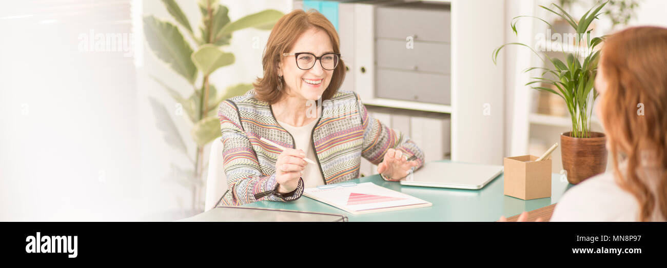 Smiling, experienced advisor talking to her female patient during therapy - Stock Image