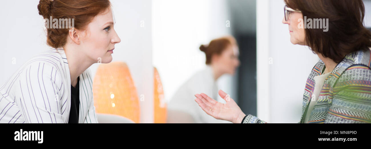 Professional therapist explaining treatment to her female patient - Stock Image
