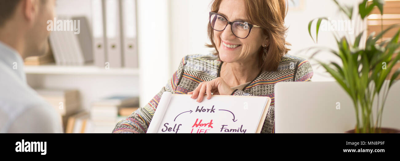 Smiling personal life coach showing a graph about work-life balance to her patient - Stock Image