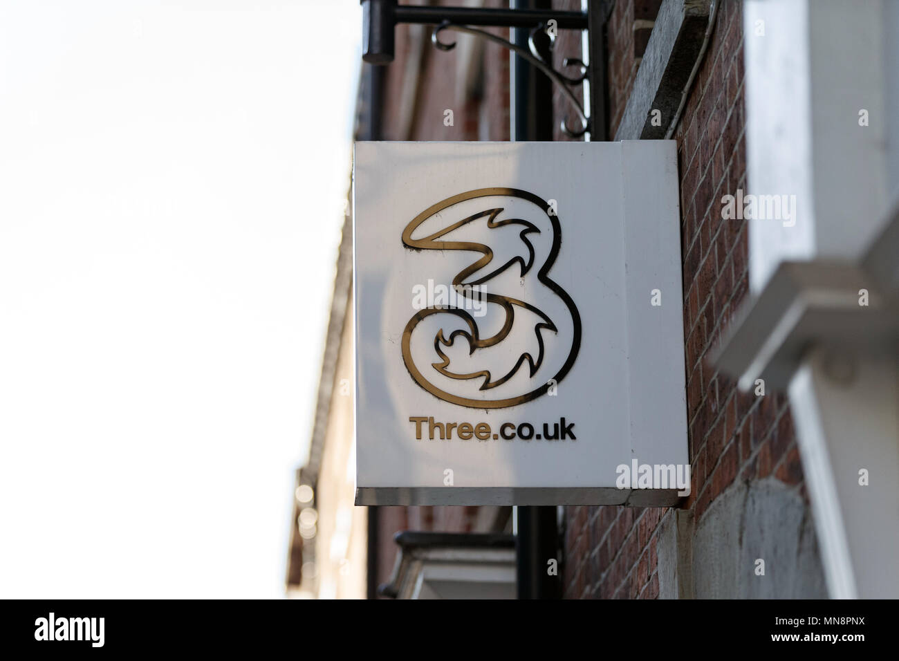 A high street branch of mobile network provider Three in the United Kingdom / Three logo, Three sign, Three high street. - Stock Image
