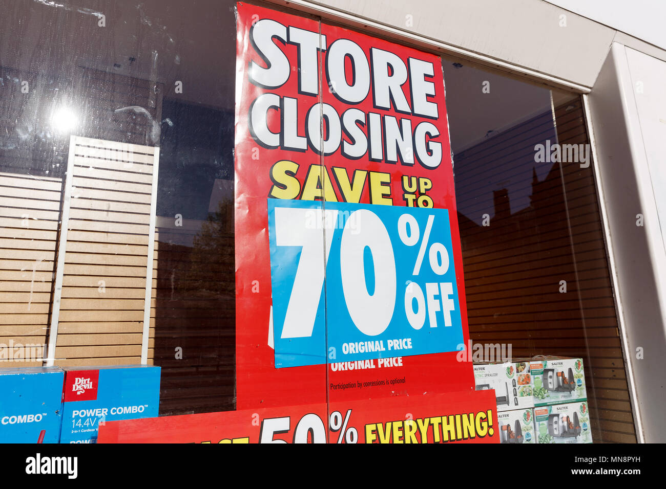 A high street store advertising a store closing down sale with up to 70% off. - Stock Image