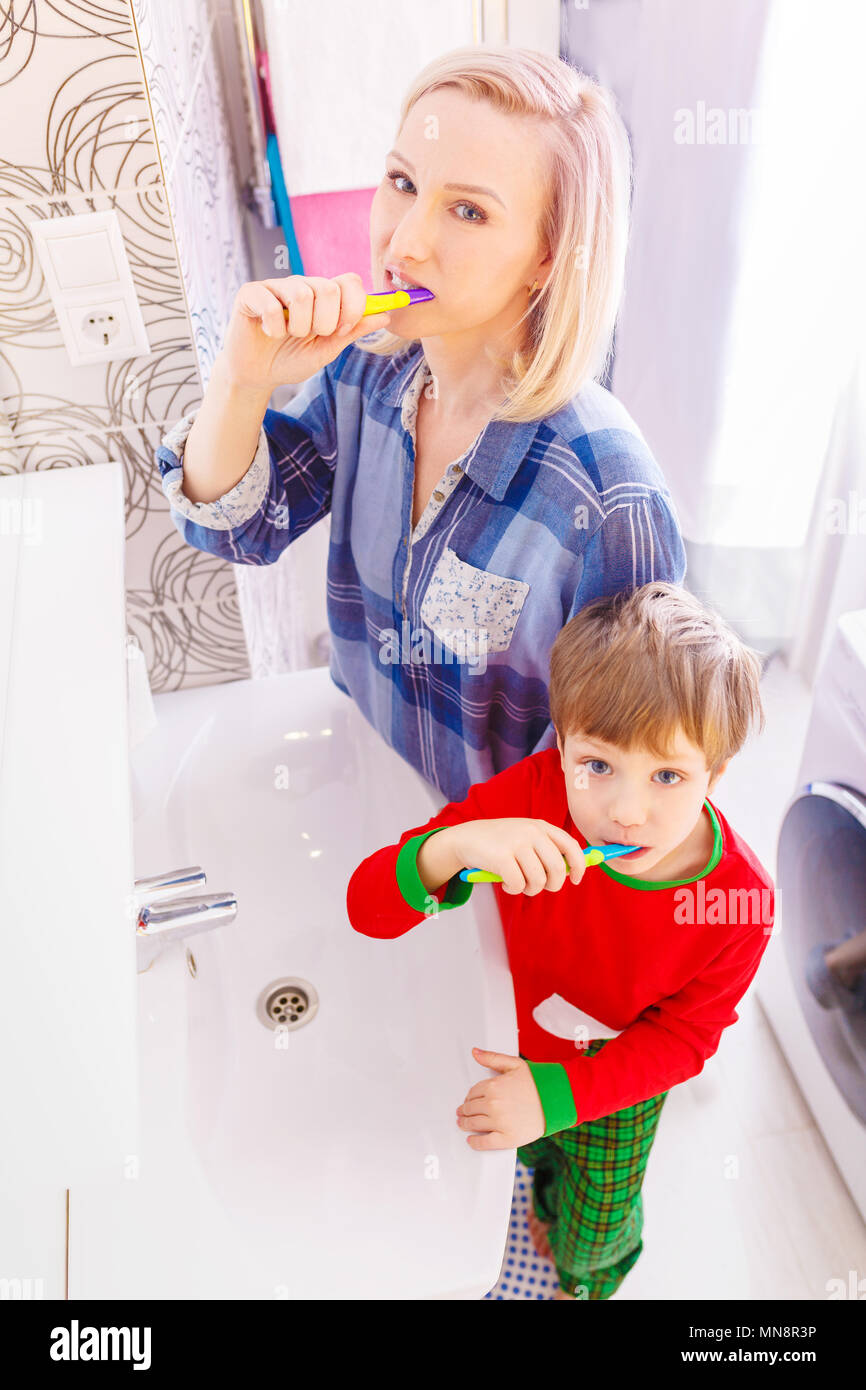 Young happy family. Mother and child little boy cleans teeth with a toothbrush in the bathroom. Healthy Mom and baby Stock Photo