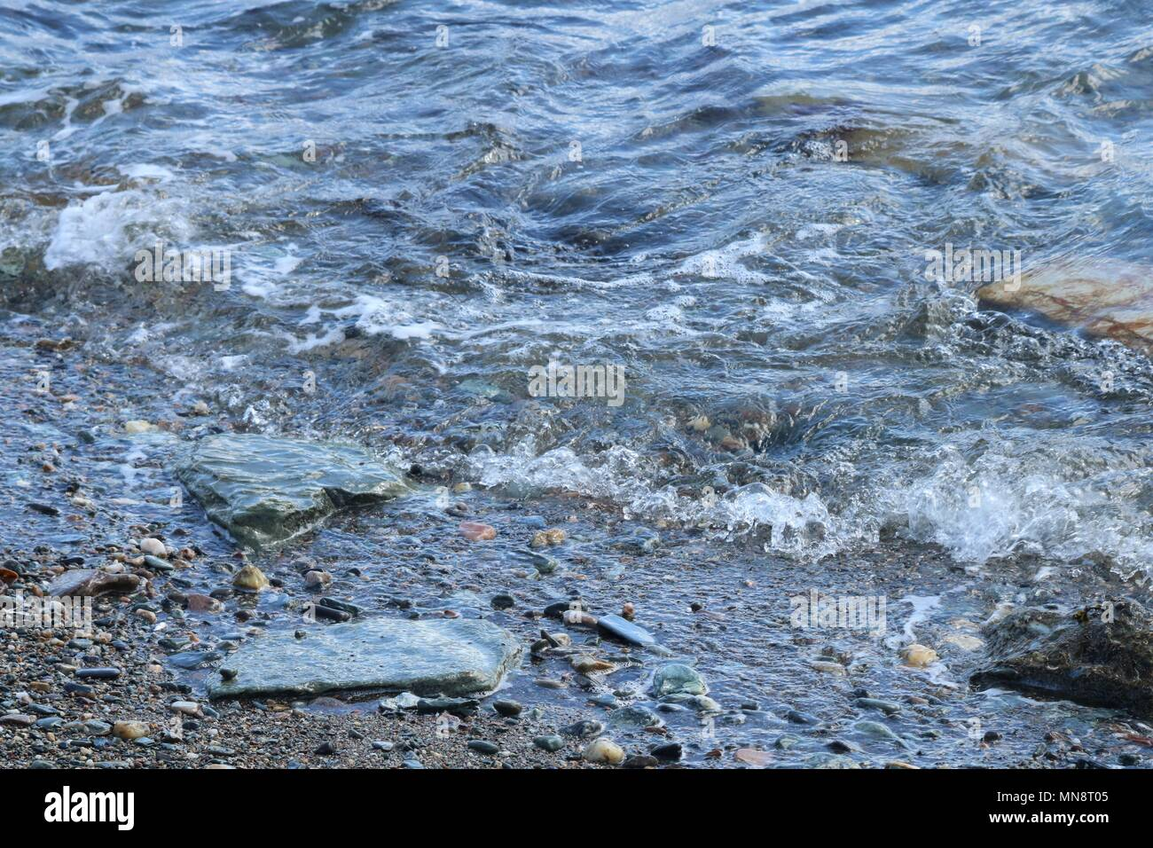 Gentle waves lapping against small rocks on a peddle beach on a sunny day. - Stock Image