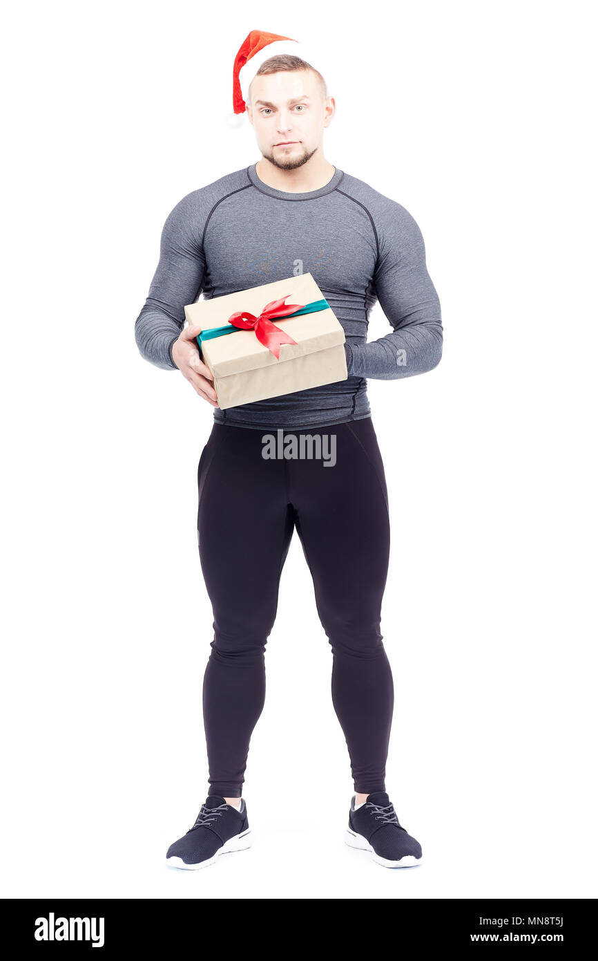 Portrait of athletic man wearing sports clothes and Santa hat and holding gift box - Stock Image