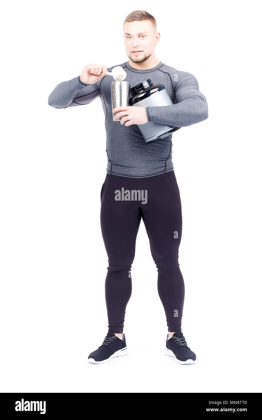 Isolated portrait of athletic man pouring sports nutrition into shaker - Stock Image