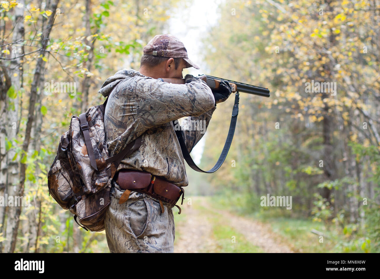 hunter in camouflage taking aim from a shotgun in the wildfowl Stock Photo