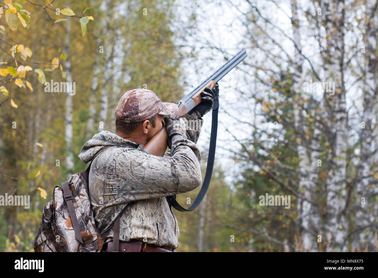 hunter taking aim in the wildfowl in the autumn forest Stock Photo