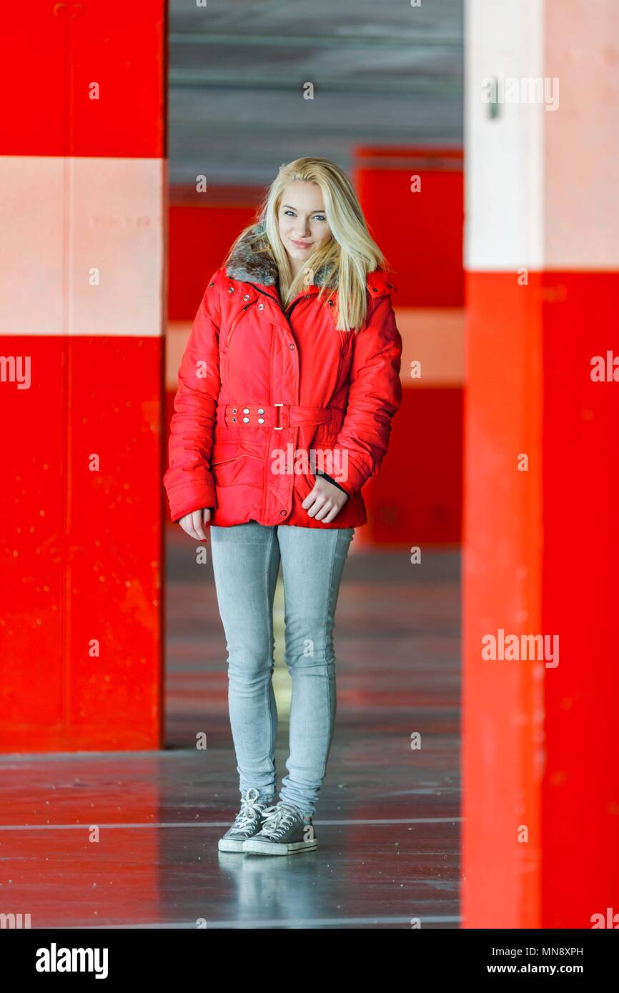 Fair blond haired teen standing in Red jacket and denim pants - Stock Image